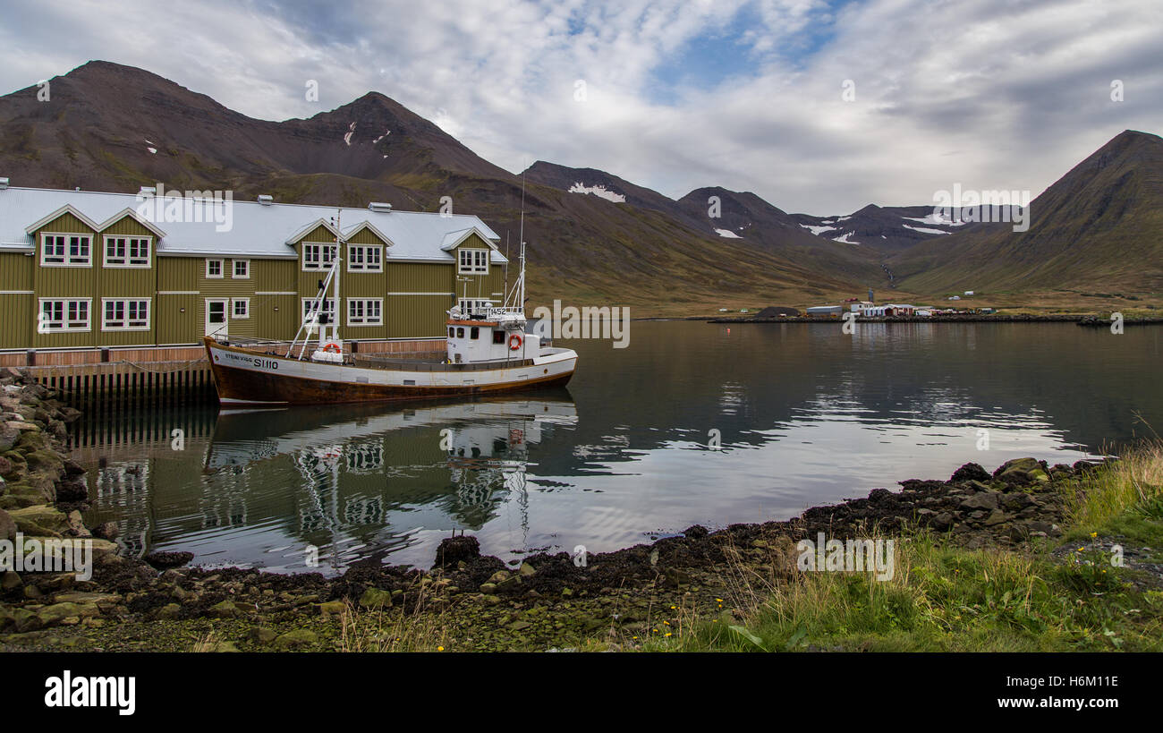 Boat next to a hotel with mountains in the background in Siglufjörður, Iceland - Stock Image