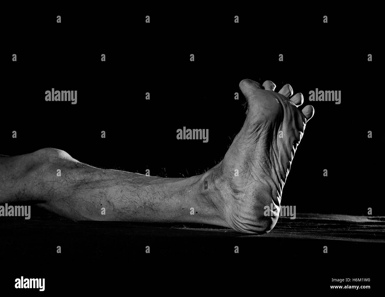 Dirty foot barefooted men against a dark background. - Stock Image