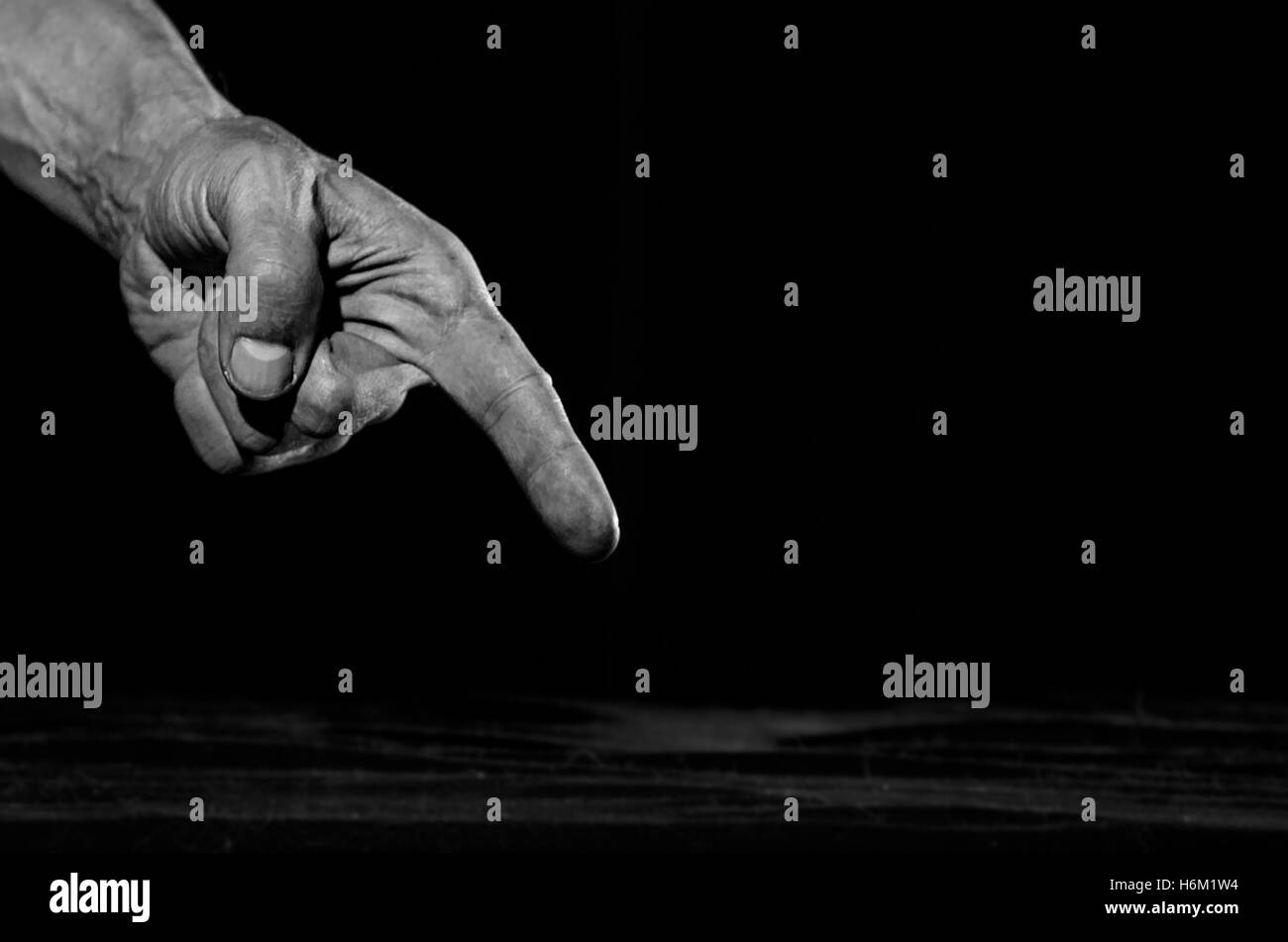 Dirty hand pointing a finger at something. - Stock Image