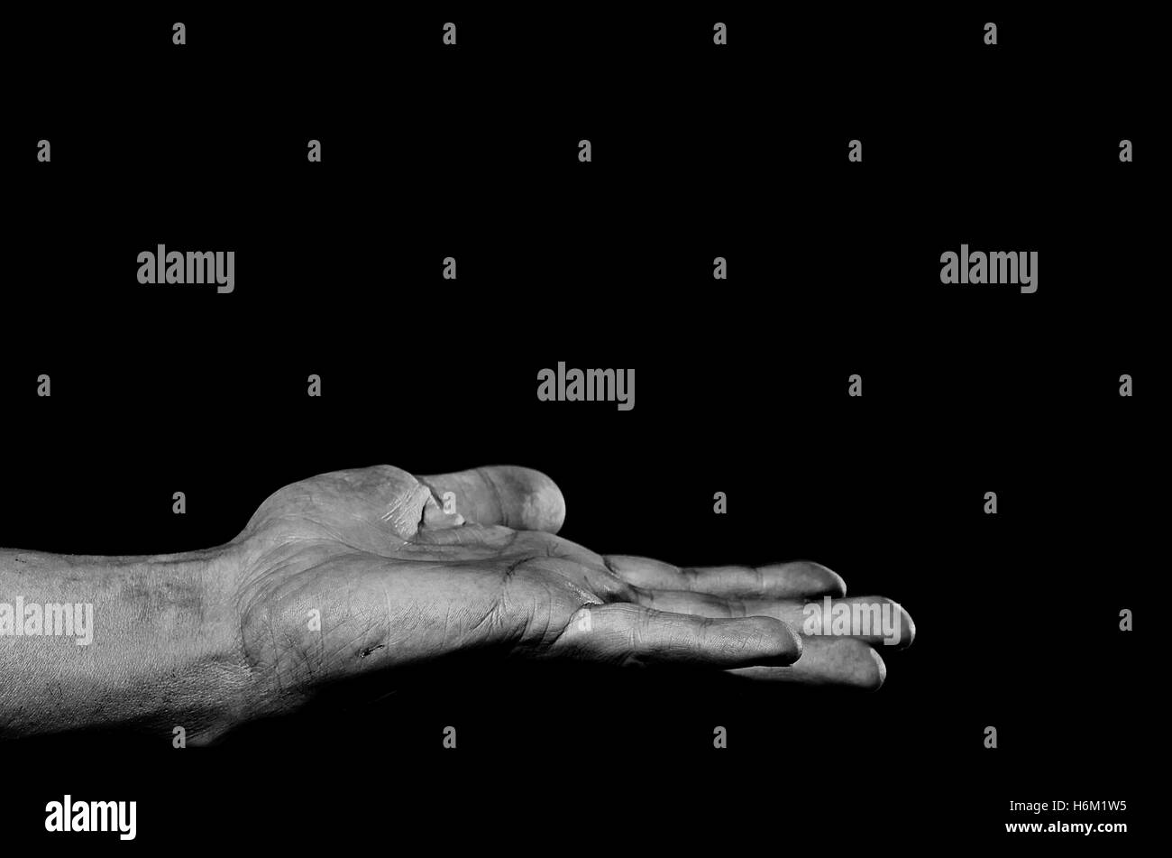 Disclosed palm up dirty man's hand on a dark background. - Stock Image