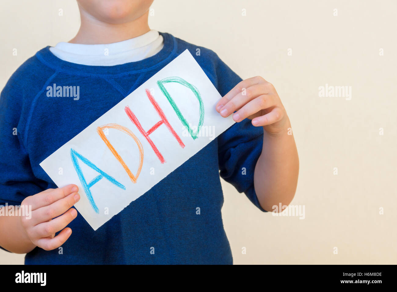 Young boy holds ADHD text written on sheet of paper. ADHD is Attention deficit hyperactivity disorder. - Stock Image
