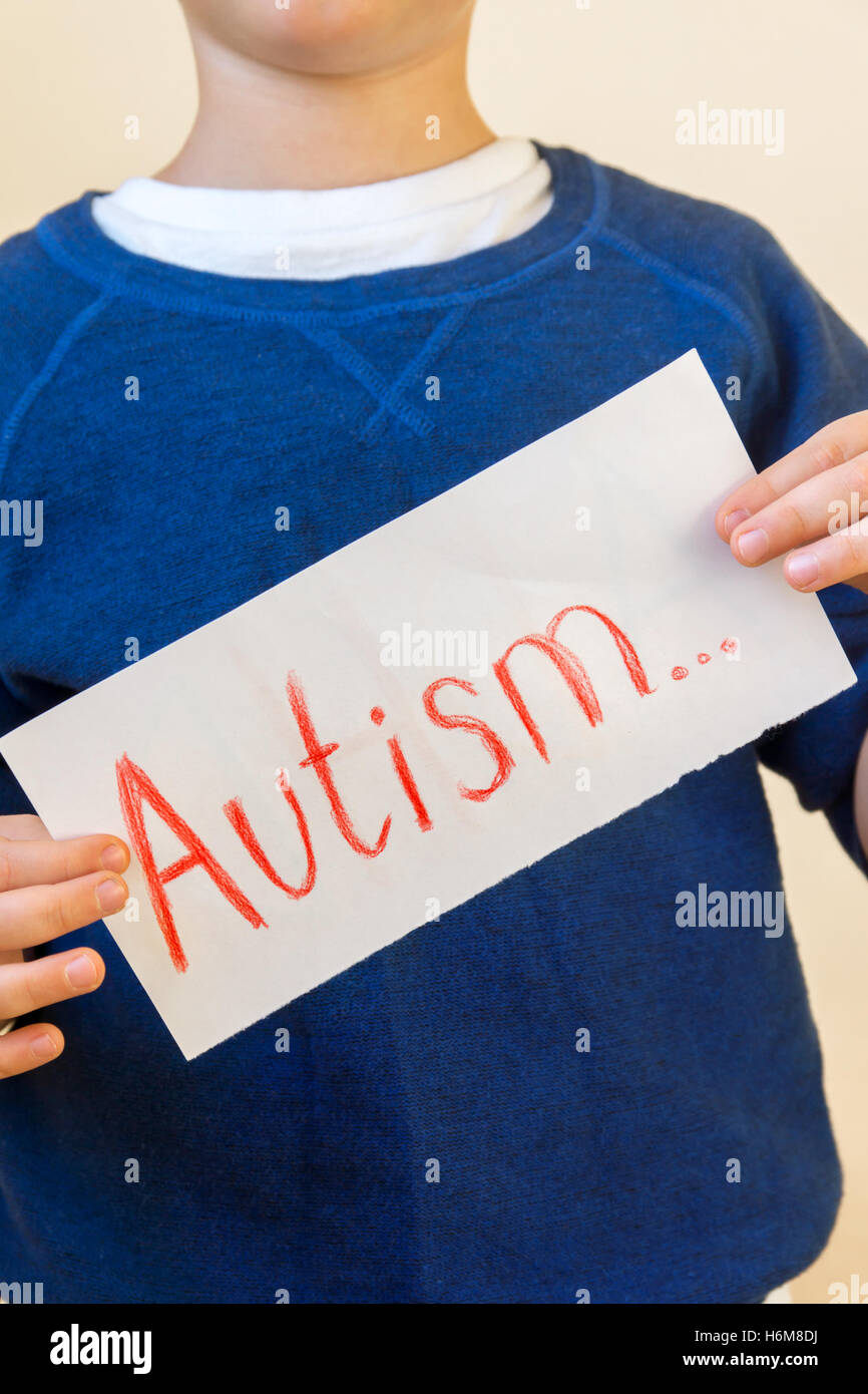 Young boy (children hands) hold Autism text written on sheet of paper close up. - Stock Image