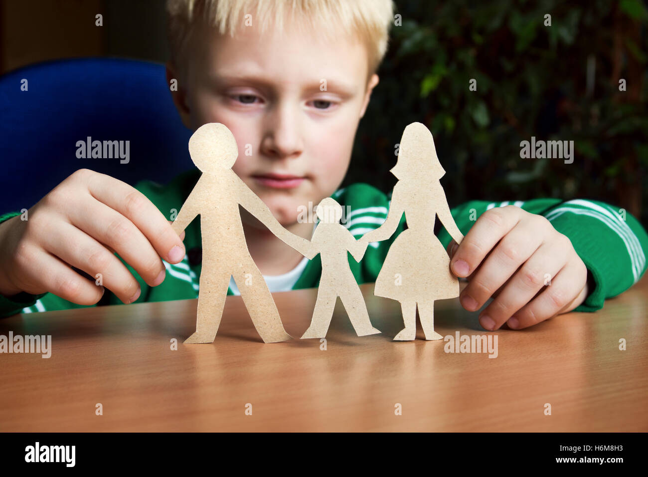 Confused child with paper family, custody, family problems, divorce, suffer concept - Stock Image