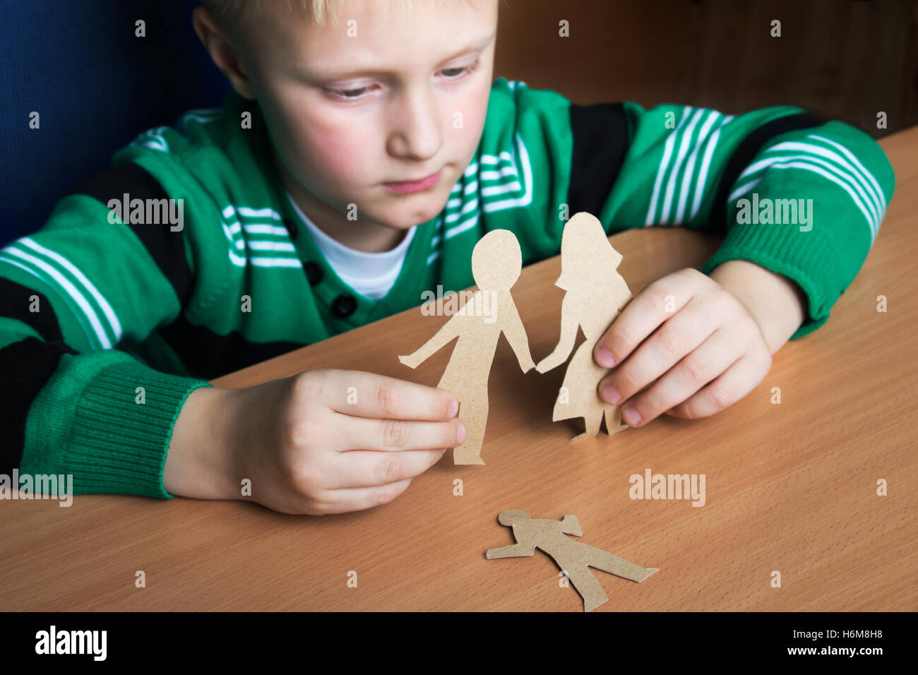 Confused child with broken paper family, custody, family problems, divorce, suffer concept - Stock Image