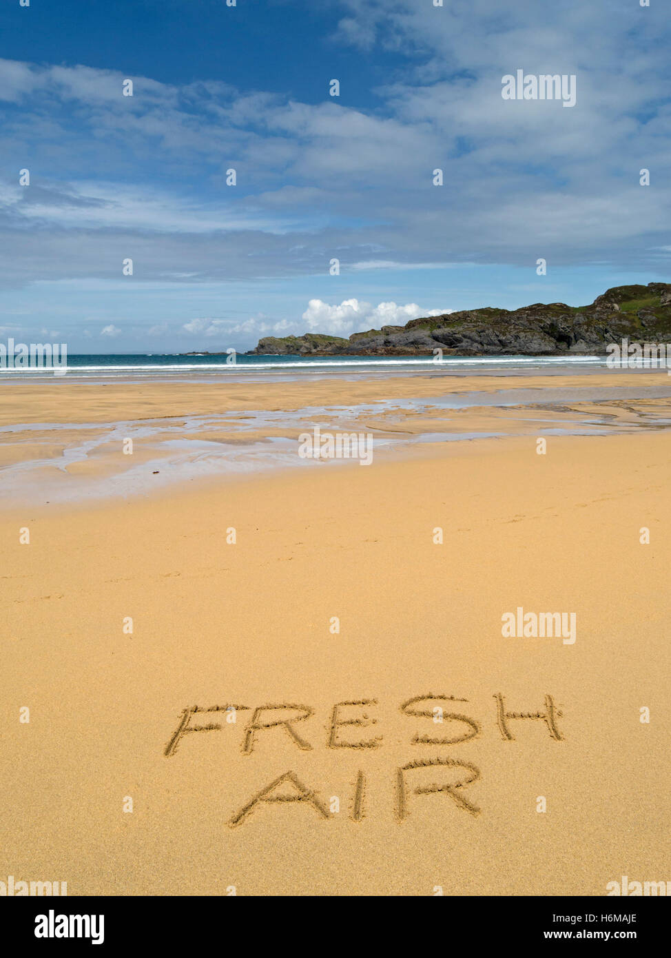 The words 'Fresh Air' written in golden yellow sand of deserted, remote remote Scottish beach. - Stock Image
