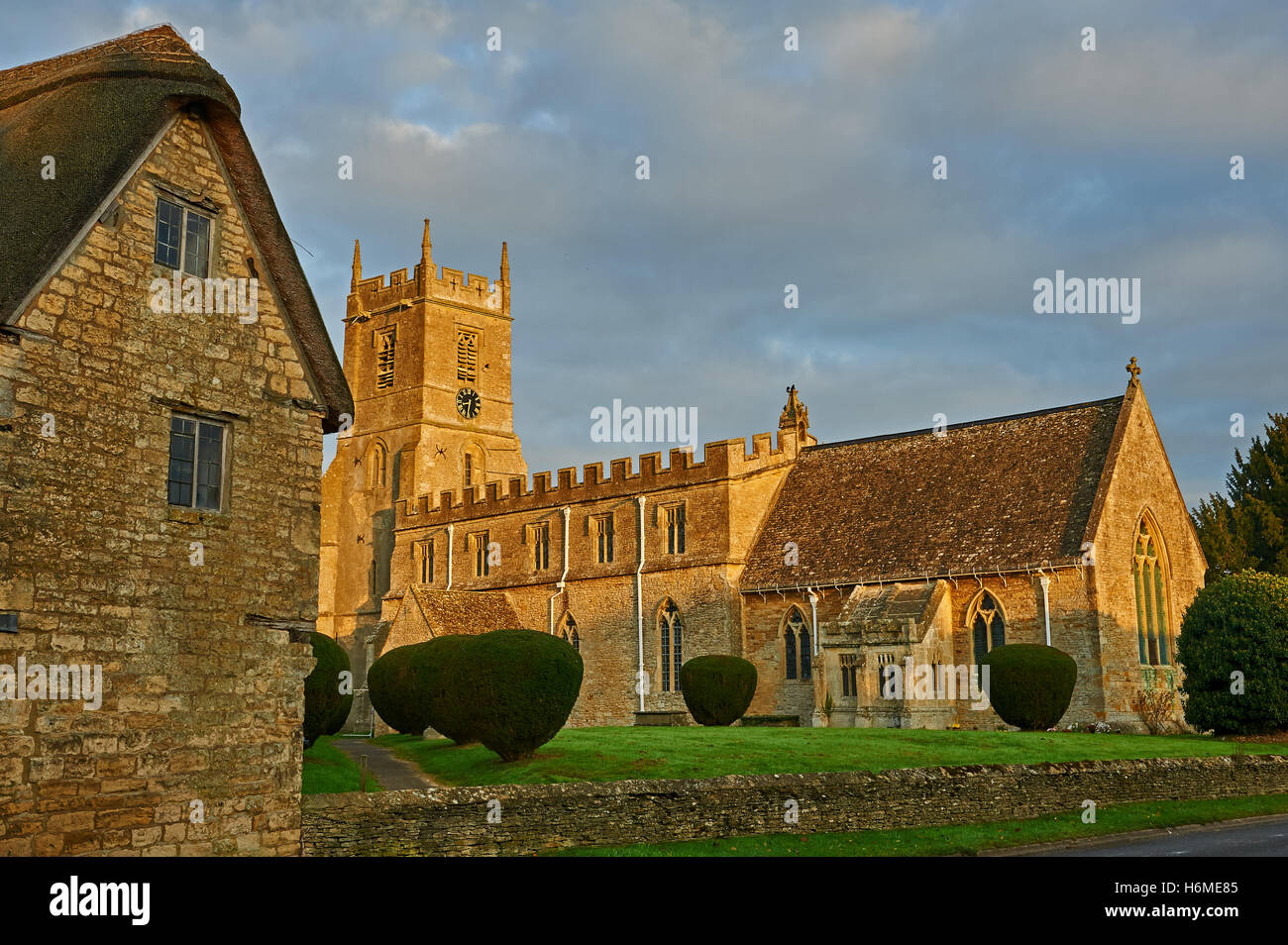 Long Compton parish church and the unusual thatched lych gate entrance with early morning sunshine. - Stock Image