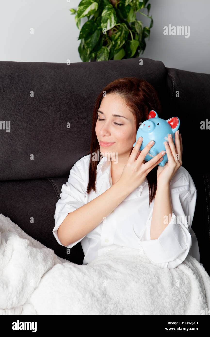 Young woman on her couch with a piggy bank thinking about his future - Stock Image