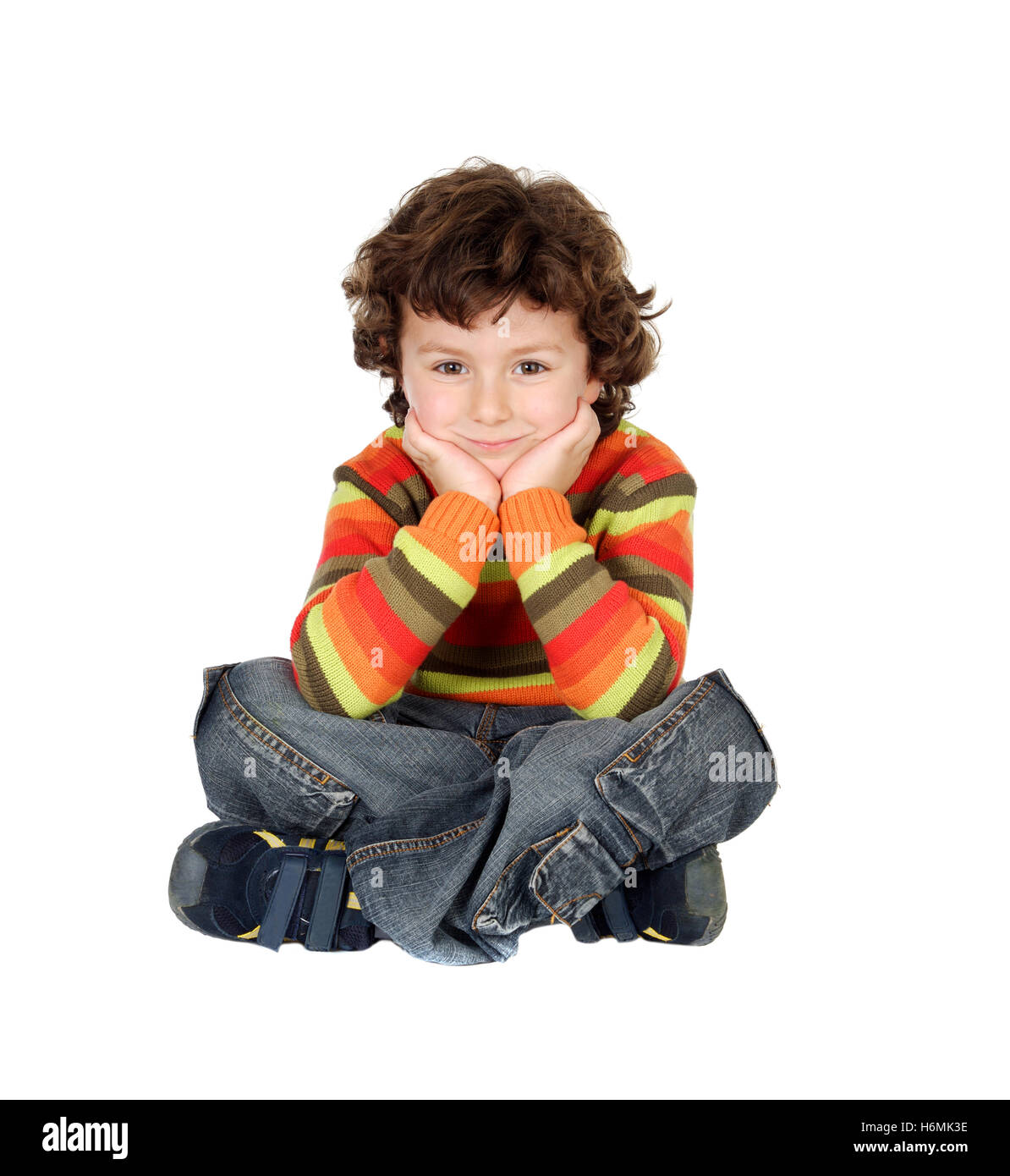 Nice boy with seven years old sitting on the white floor thinking - Stock Image