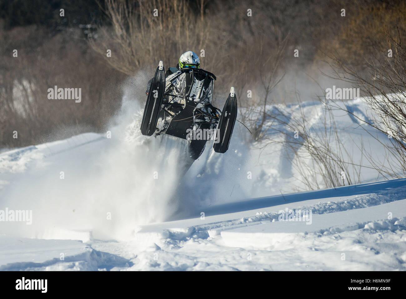 Man on snowmobile in winter mountain - Stock Image