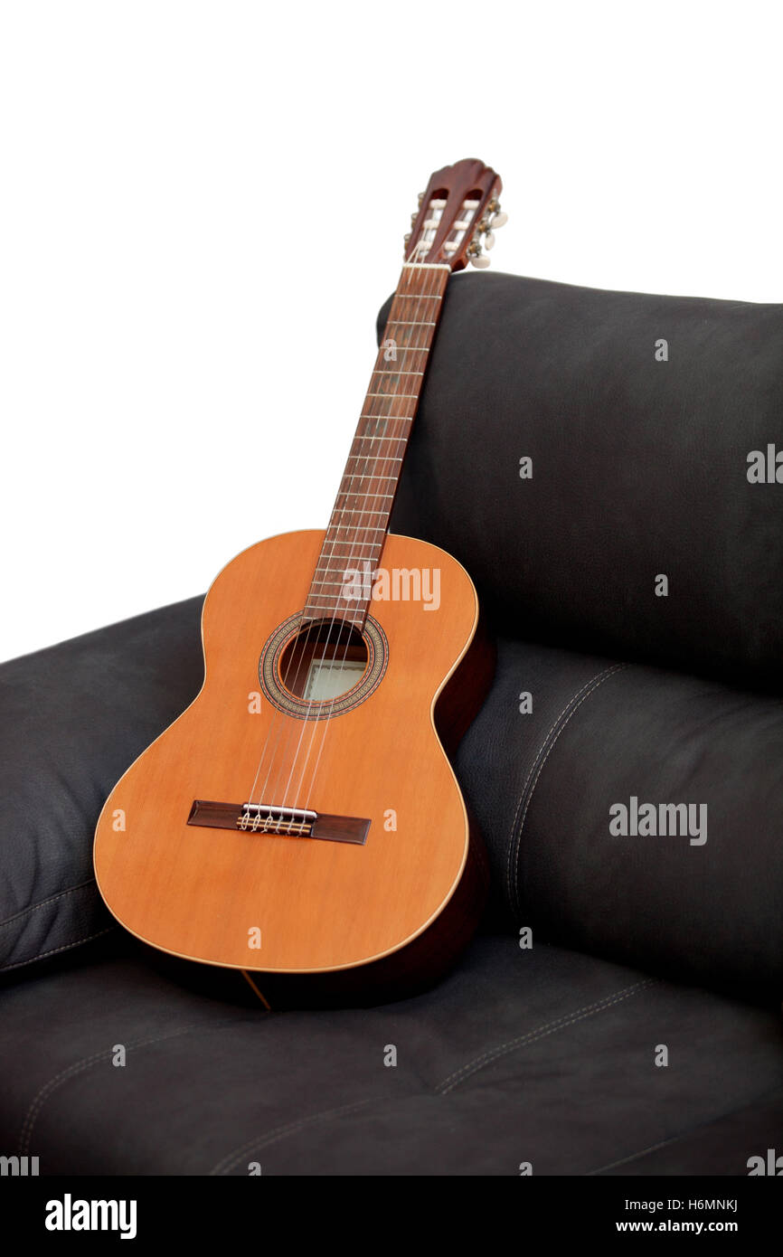 Wooden classical guitar on the grey sofa - Stock Image