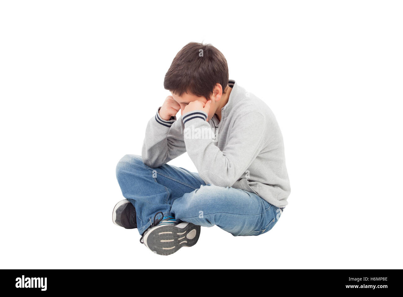 Sad preteen boy sitting on the floor isolated on a white background - Stock Image
