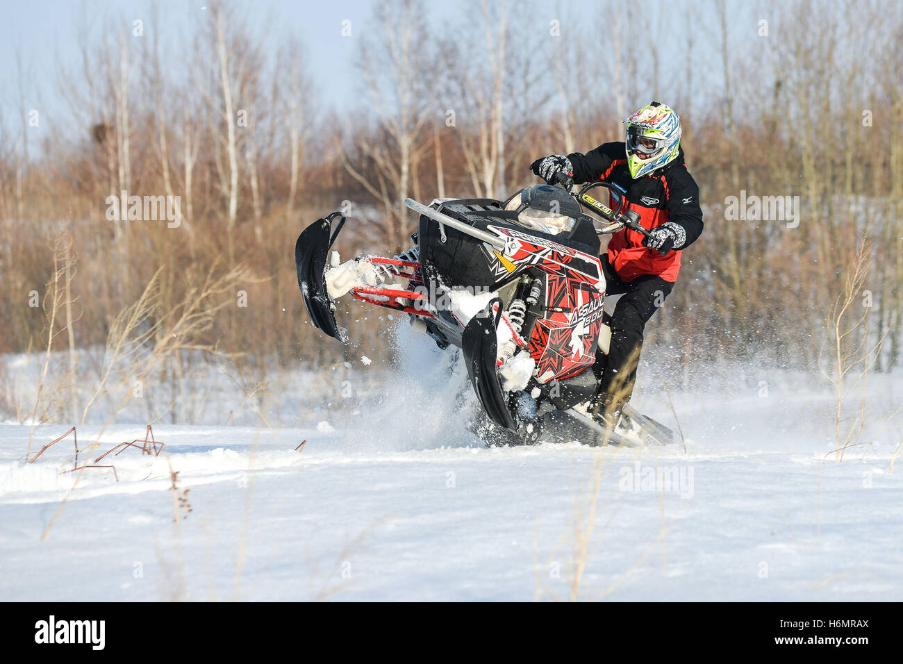 man and fast action snowmobile jumping - Stock Image