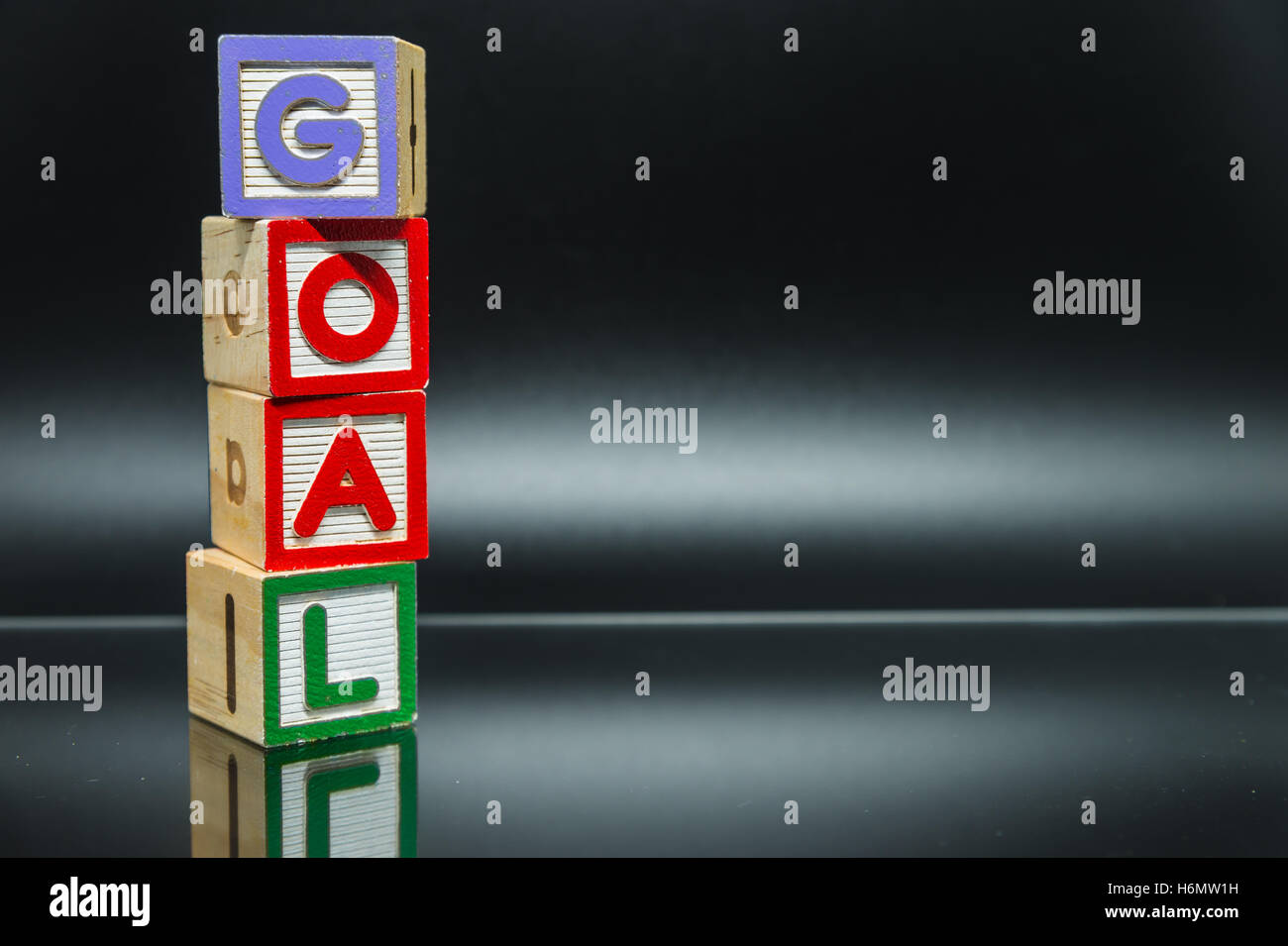GOAL word wooden block arrange in vertical style on black background and selective focus - Stock Image