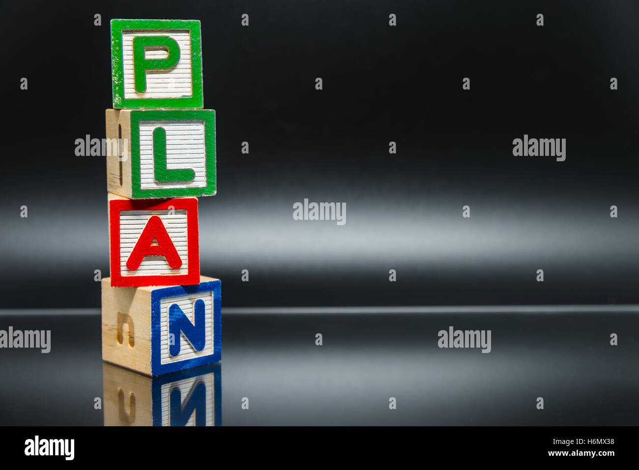 PLAN word wooden block arrange in vertical style on black background and selective focus - Stock Image