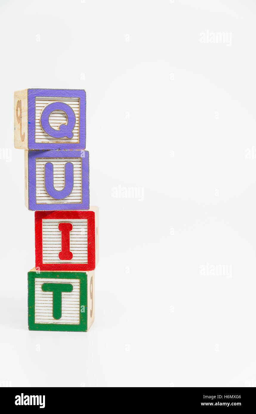 QUIT word wooden block arrange in vertical style on white background and selective focus - Stock Image