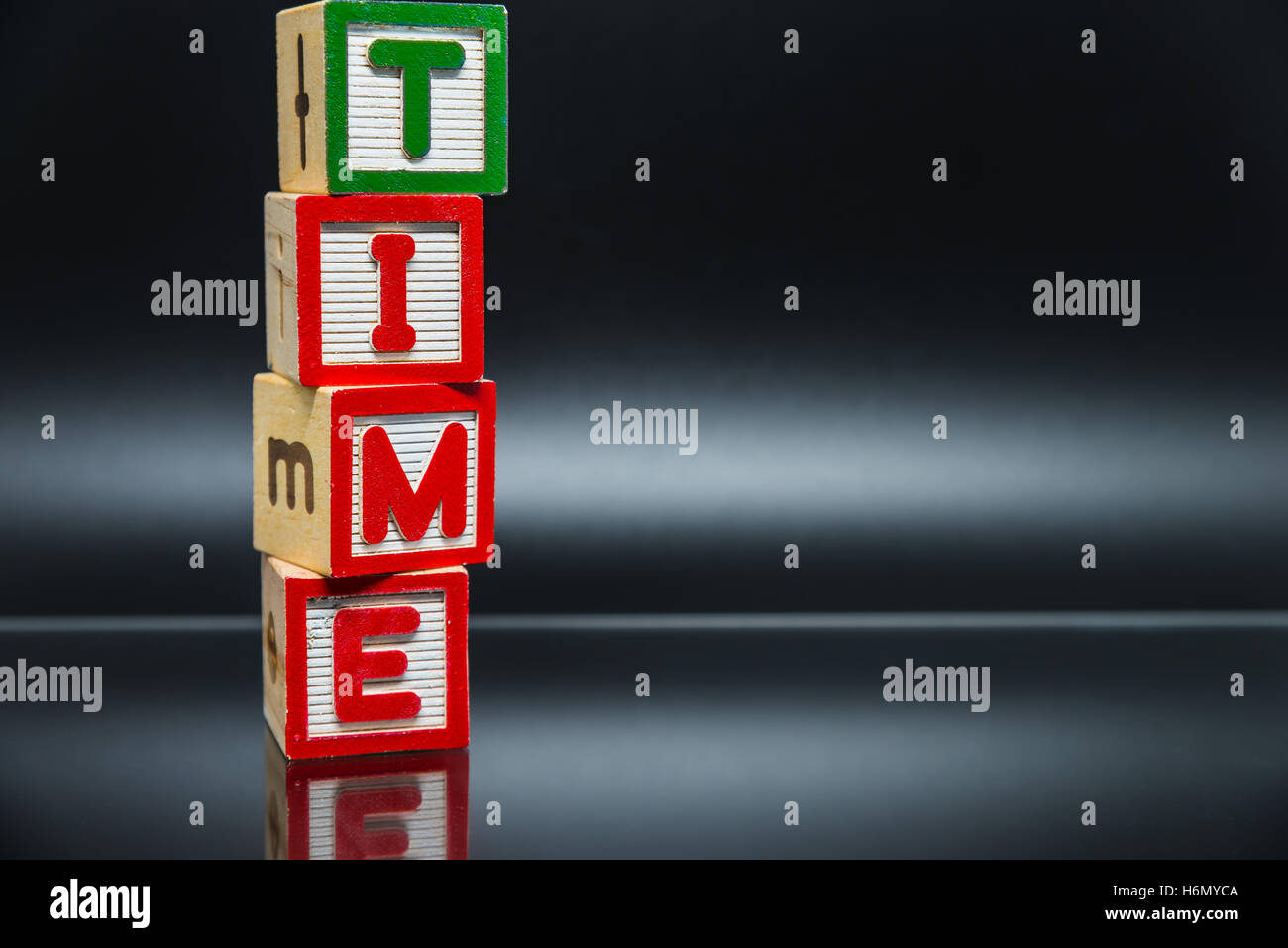 TIME word wooden block arrange in vertical style on black background and selective focus - Stock Image