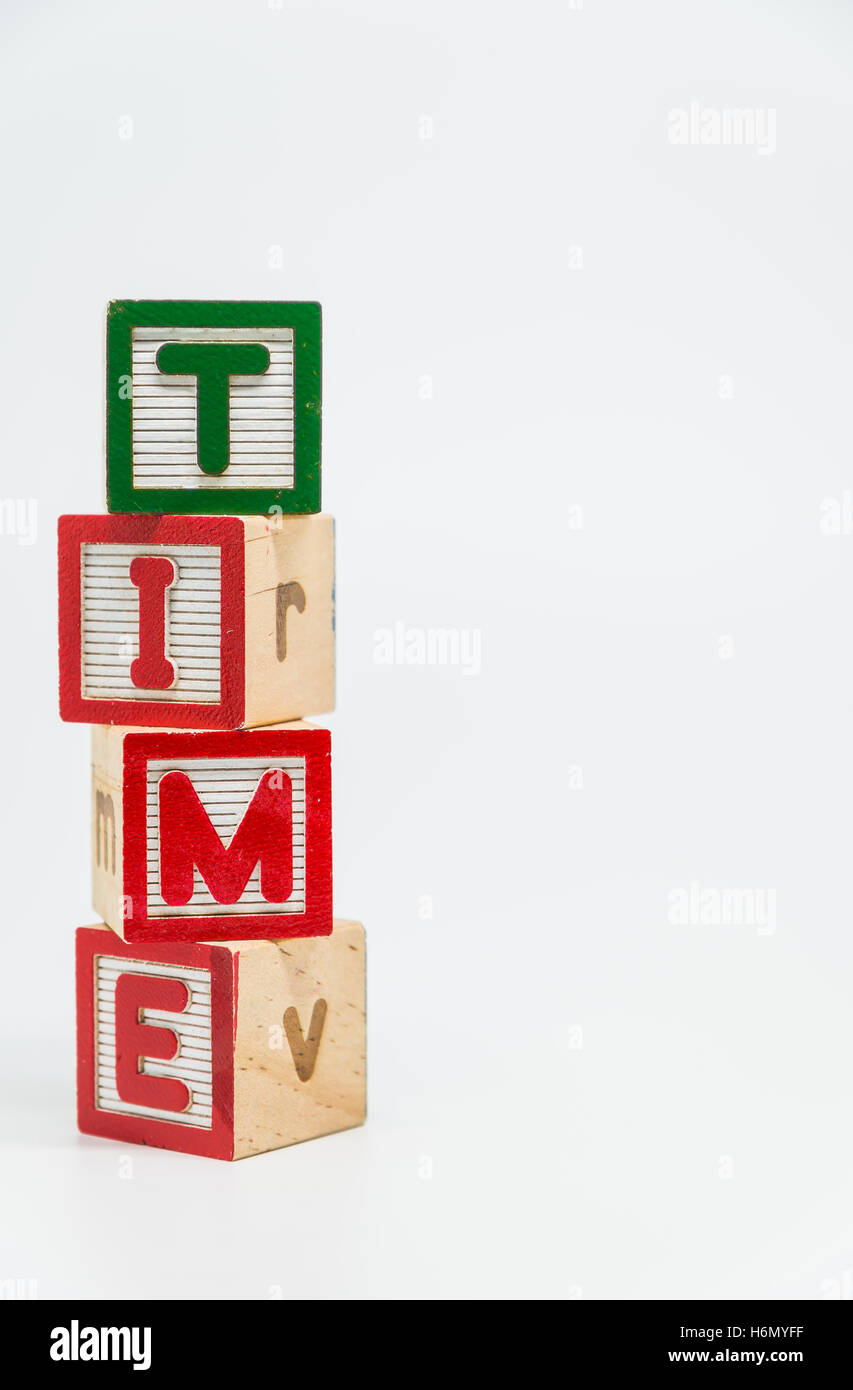 TIME word wooden block arrange in vertical style on white background and selective focus - Stock Image