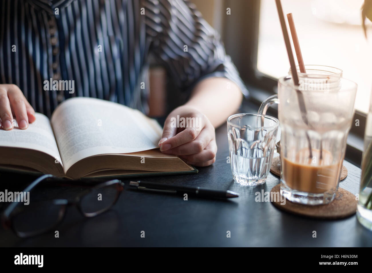 Sunday morning lifestyle scene of young hipster woman reading book in cafe with. Weekend activity or hobby concept Stock Photo