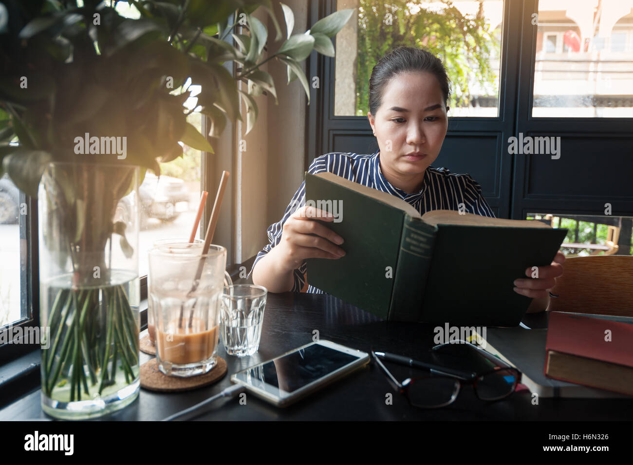 Sunday morning lifestyle scene of young hipster asian woman reading book in cafe with. Weekend activity or hobby Stock Photo