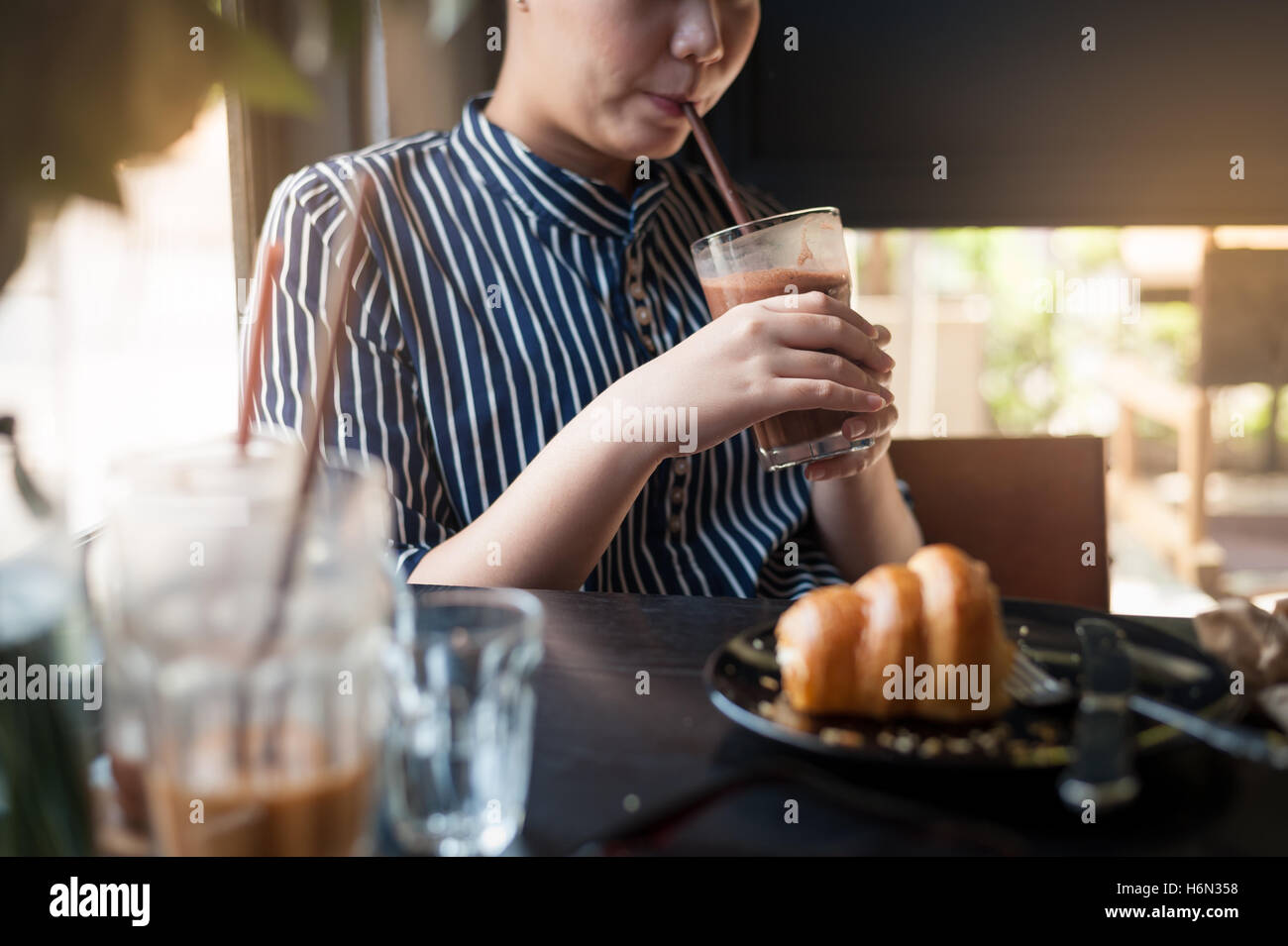 Weekend afternoon lifestyle and activity of young hipster woman holding and drinking iced chocolate in cafe. Sunday - Stock Image