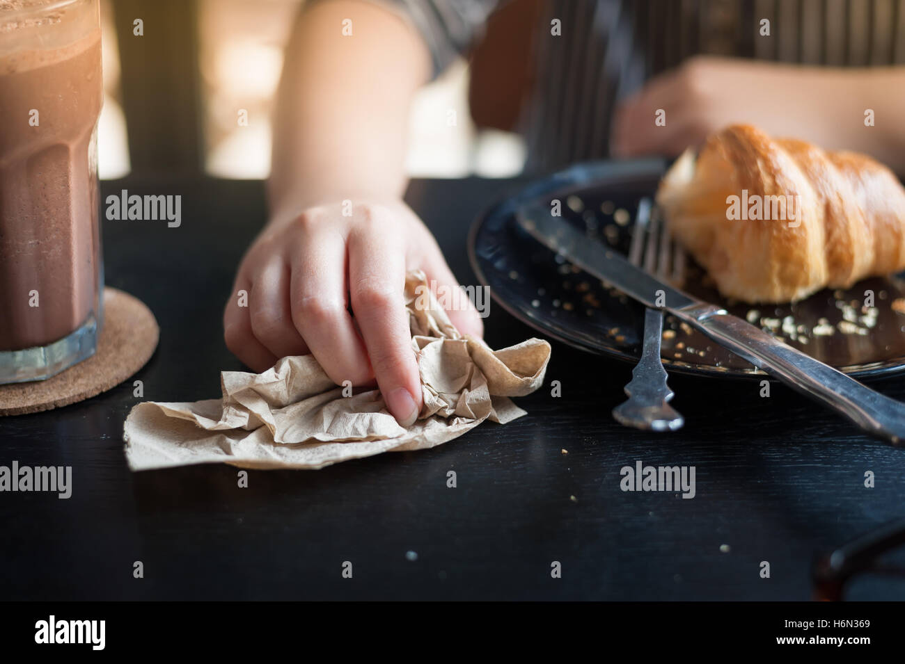 Woman right hand wipe on brown paper napkin on wood table in cafe. - Stock Image