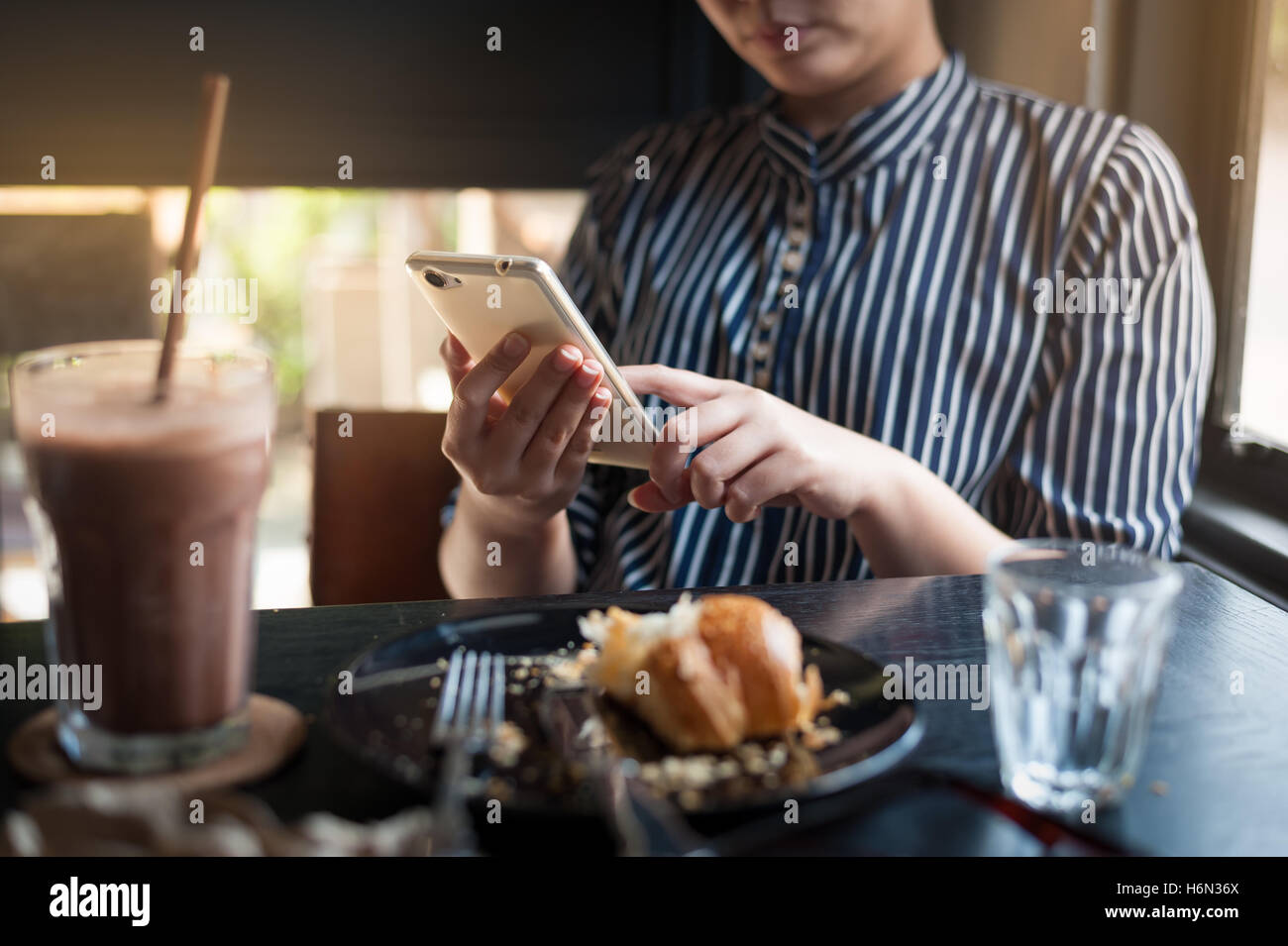 Sunday morning lifestyle scene of young hipster woman using mobile phone while sitting in cafe. Trendy lifestyle - Stock Image