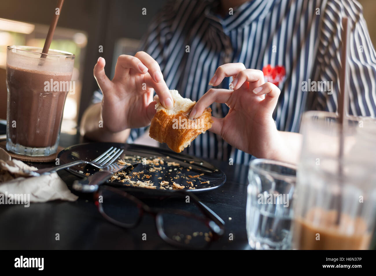 Weekend afternoon lifestyle and activity of young hipster woman eating croissant on wood table in cafe. Sunday morning - Stock Image