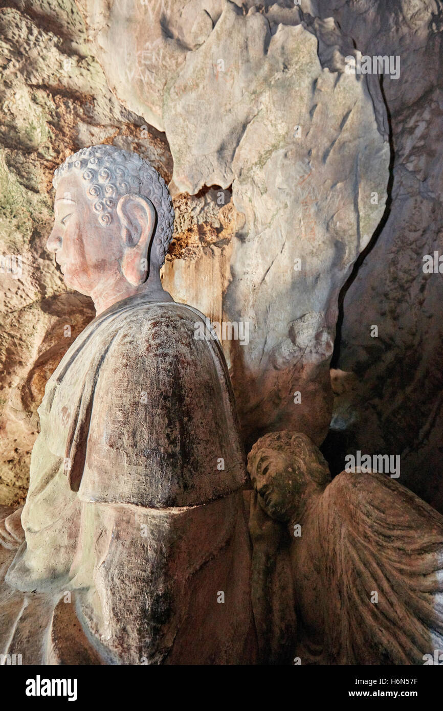 Seated and Reclining Buddha statues in Tang Chon Cave. Thuy Son Mountain, The Marble Mountains, Da Nang, Vietnam. - Stock Image