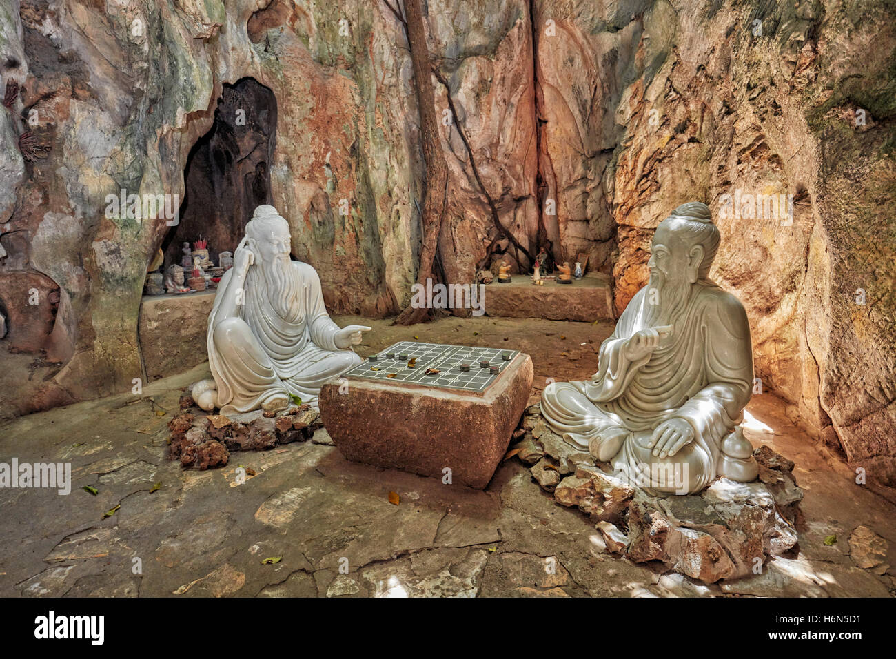 Two wise men playing Xiangqi (Chinese chess) – sculpture in Ban Co (Chess Board) Grotto in Tang Chon Cave. The Marble Stock Photo