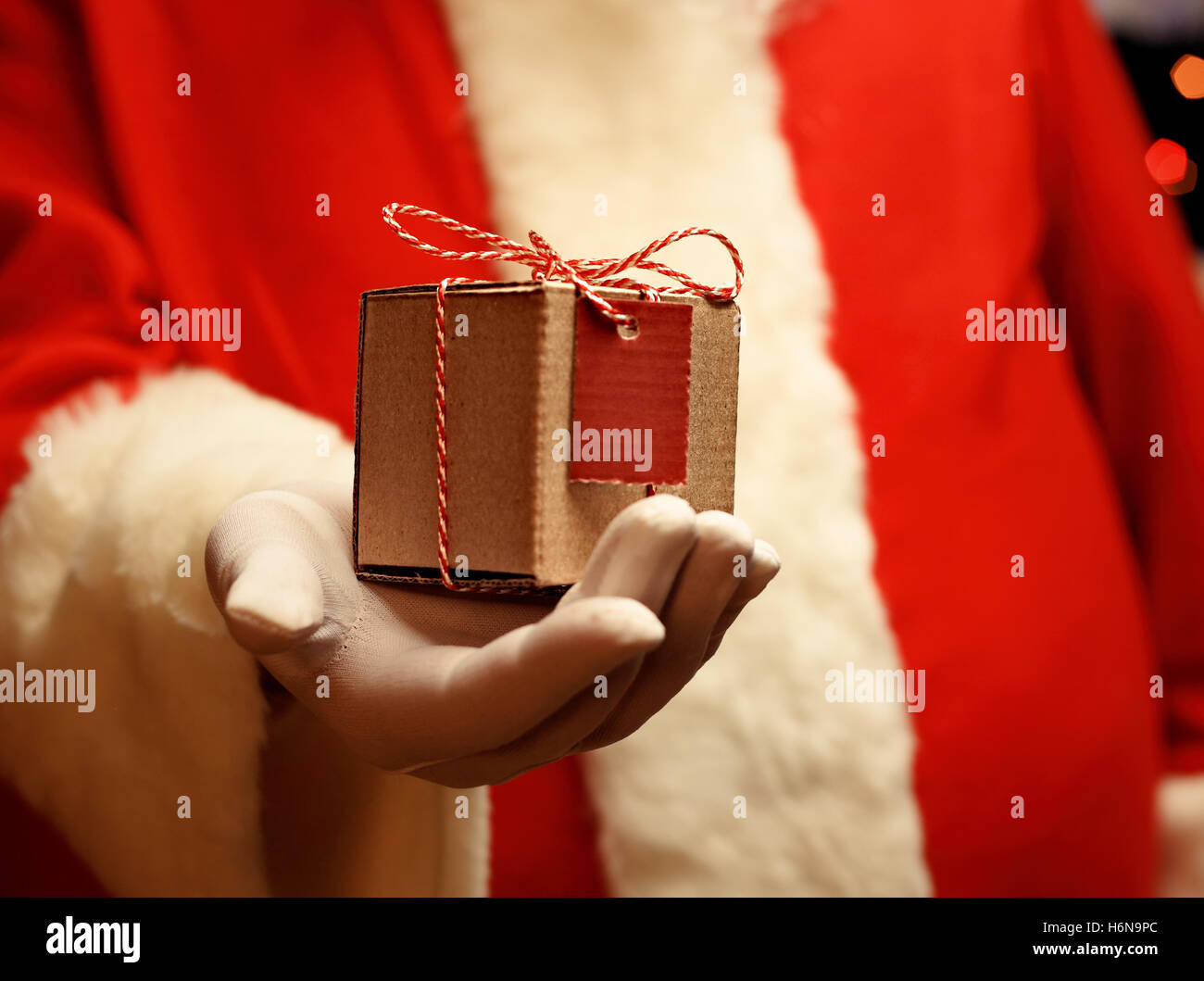 Santa Claus gloved hands holding giftbox - Stock Image