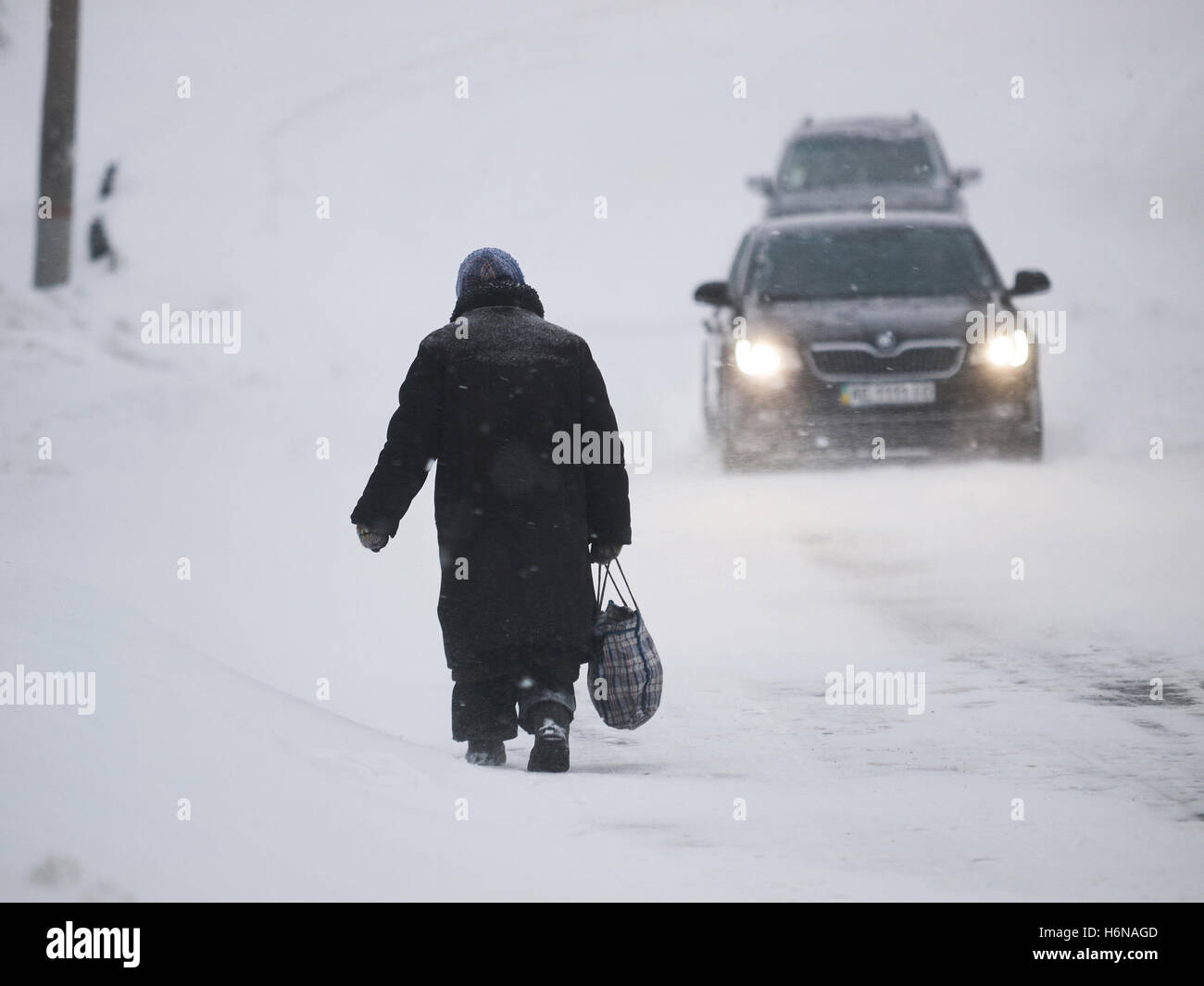 Kryvyi Rih, Ukraine - January, 18, 2016: Old indigent woman in old fur coat with shopping bag wander along the snowbound - Stock Image