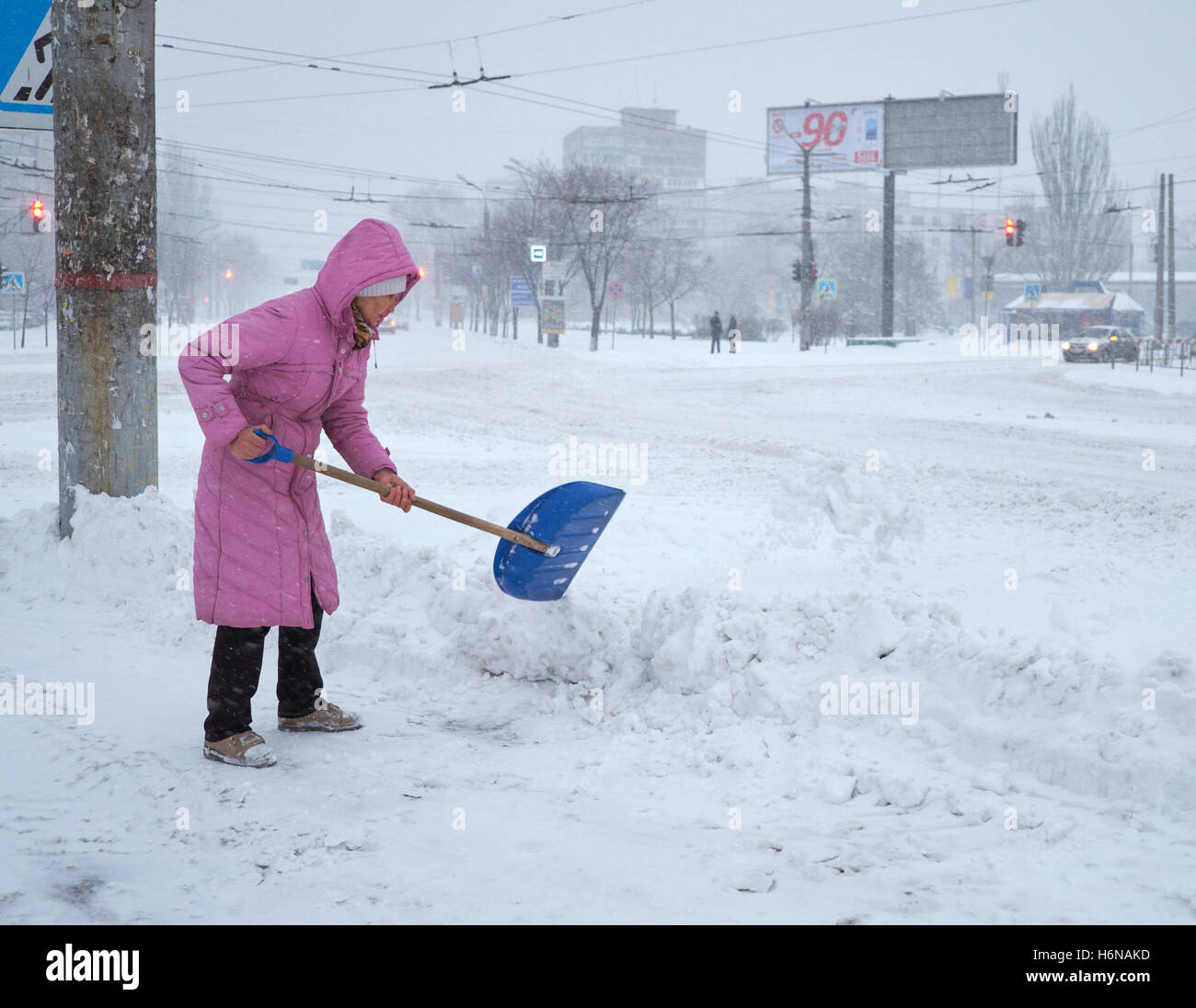 Kryvyi Rih, Ukraine - January, 17, 2016: Woman in the pink coat cleaning the snow with blue shovel from the sidewalk - Stock Image
