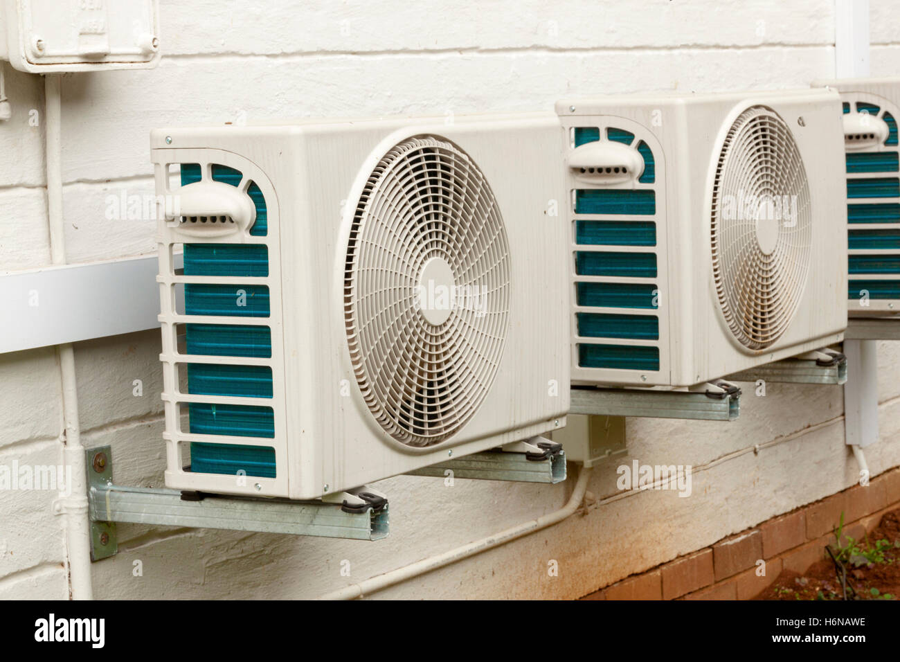 Three weathered white air conditioning unit mounted on