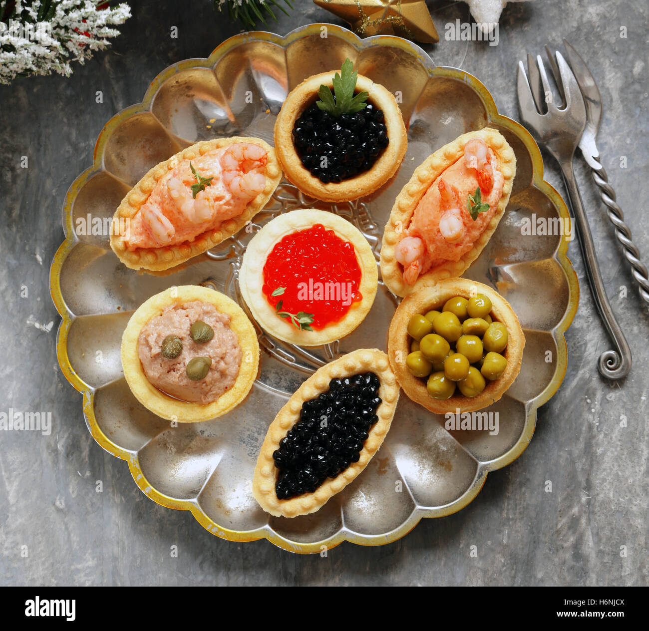 Christmas appetizers. Small tartlets with caviar and pate. Buffet and bar. - Stock Image