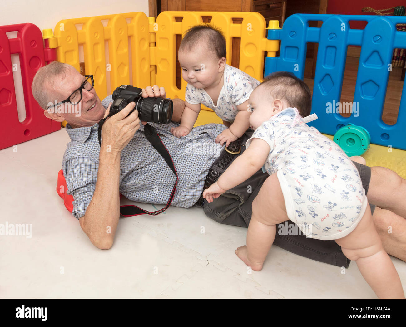 grandfather trying to photograph twin babies - Stock Image