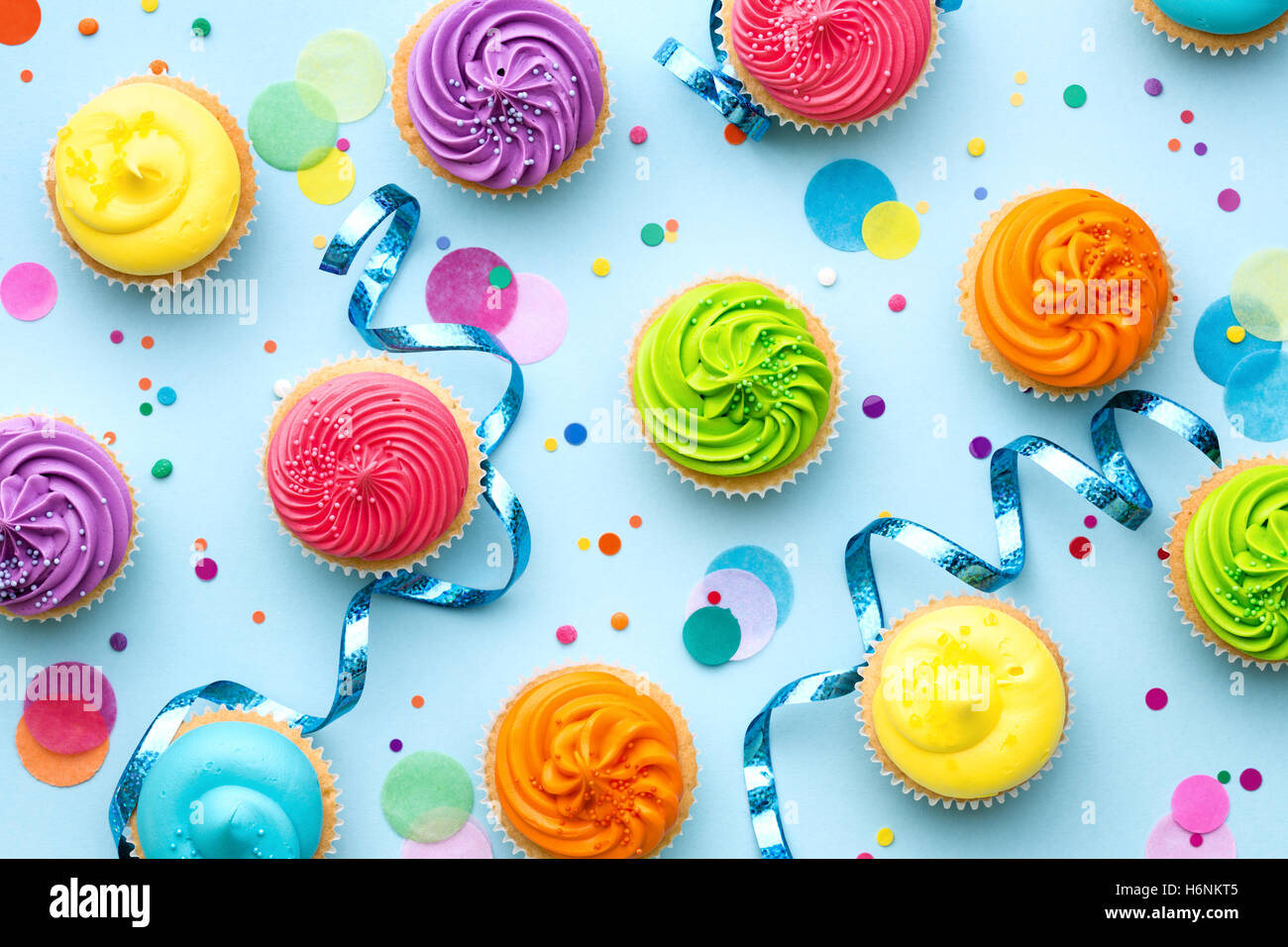 Colorful cupcake party background on blue - Stock Image