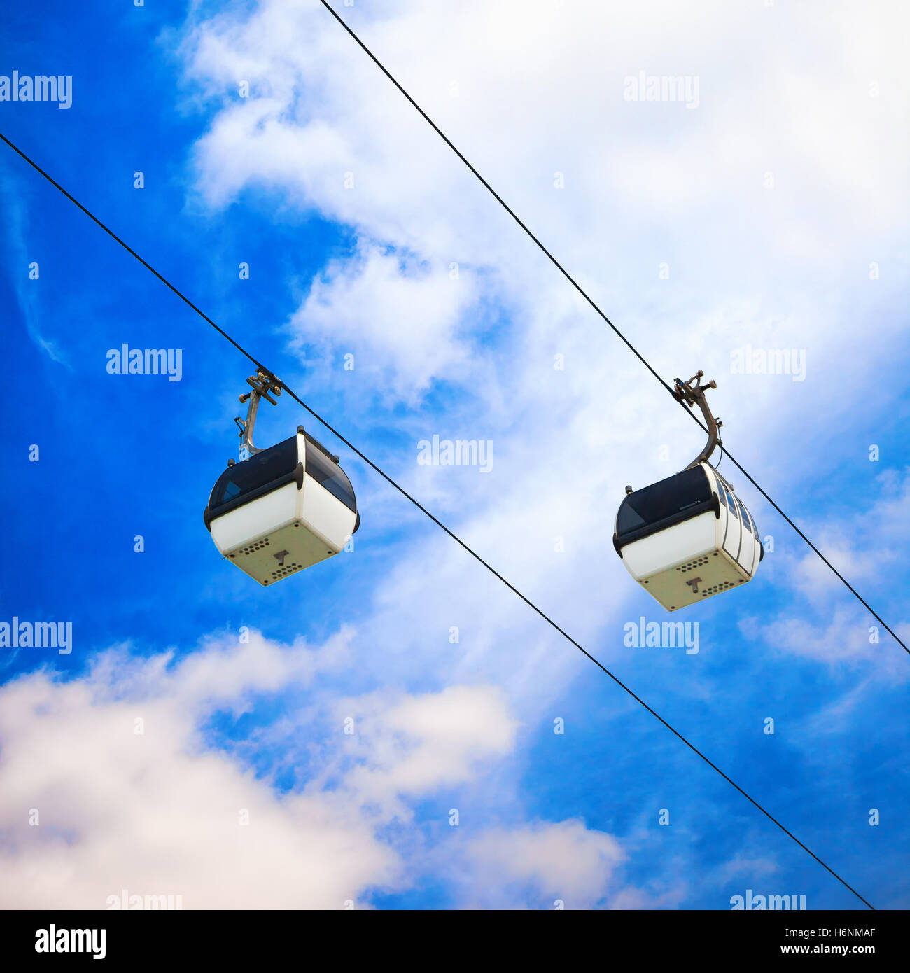 A cableway with two cable car on a partly cloudy blue sky background - Stock Image