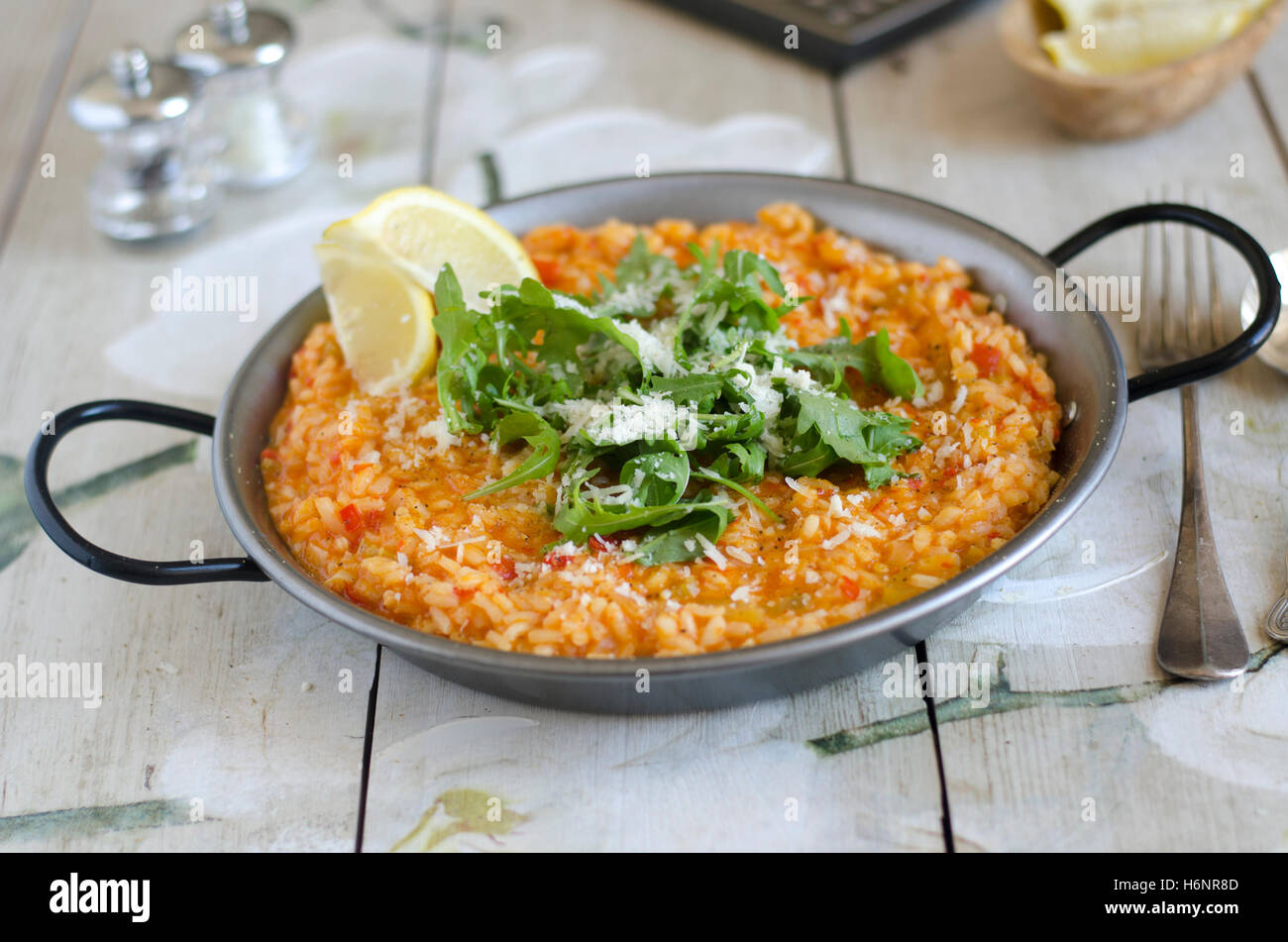 Red pepper risotto with Parmesan and rocket Stock Photo