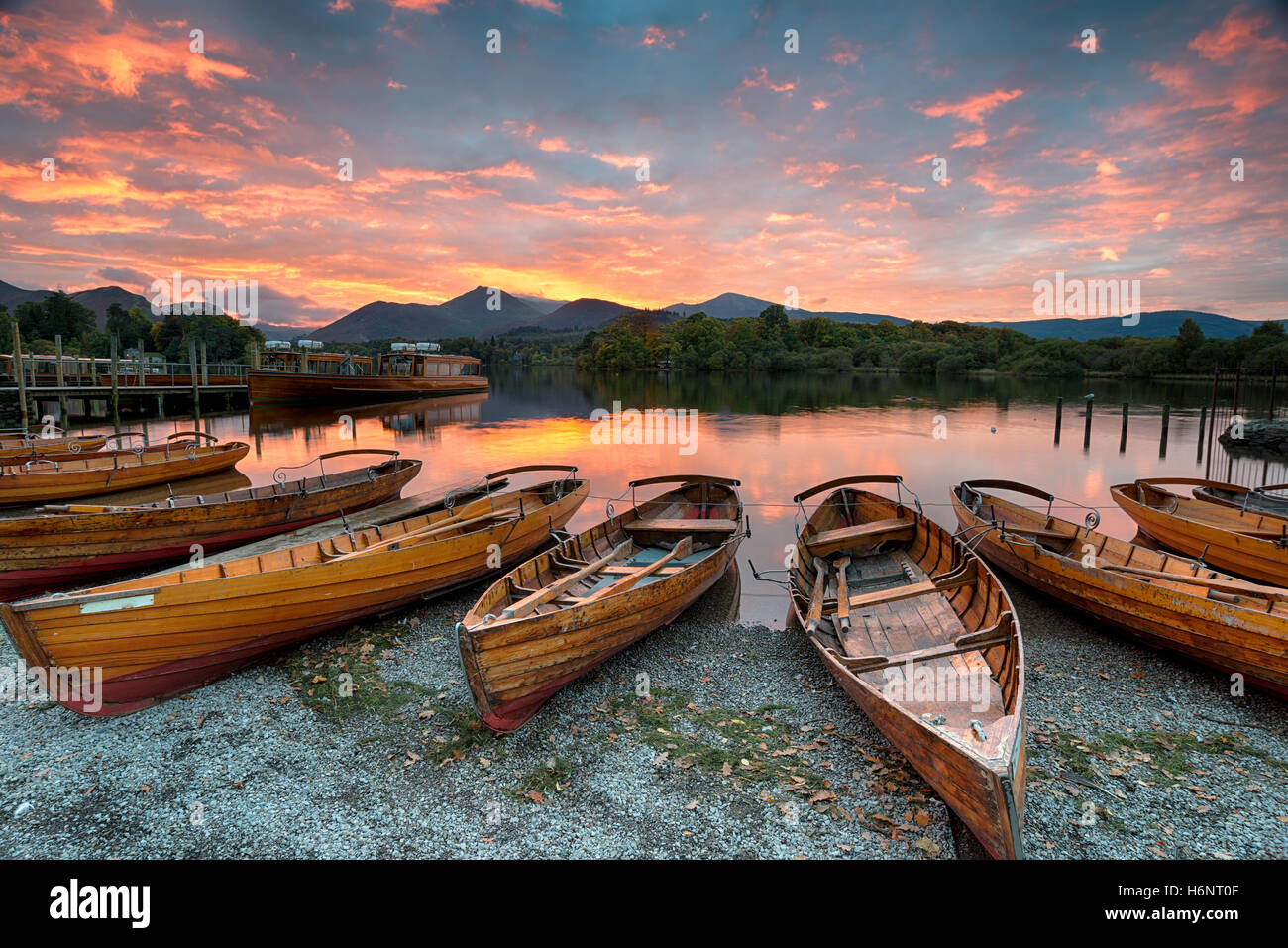 Stunning sunset over wooden rowing boats on Derwentwater at Keswick in the Lake District Nationla Park in Cumbria - Stock Image