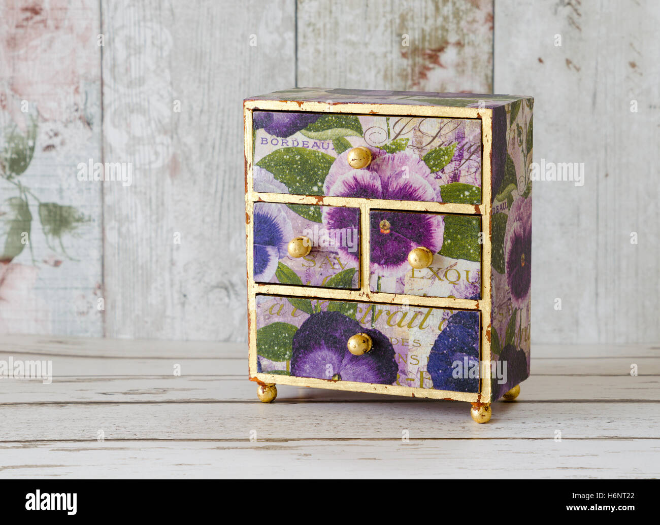 A handmade mini chest of drawers decoupaged in vintage papers and gilded with gold leaf - Stock Image