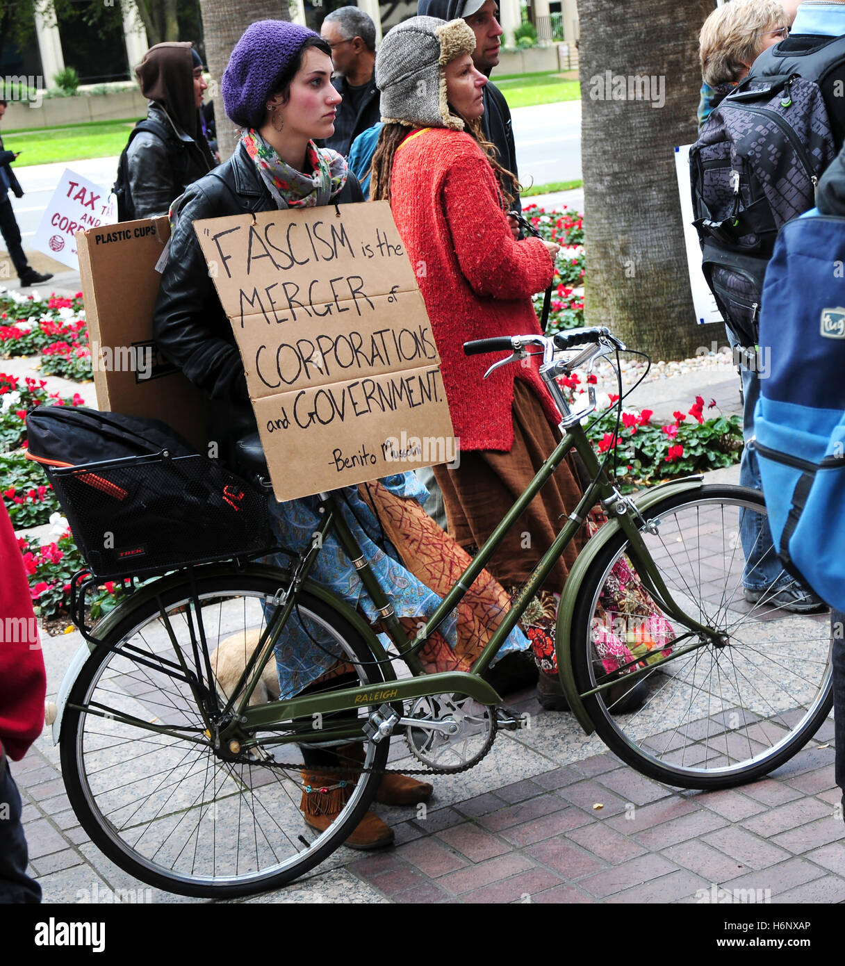A activist holding a sign reading 'Fascism is the merger of corporations and government.' at a protest of - Stock Image