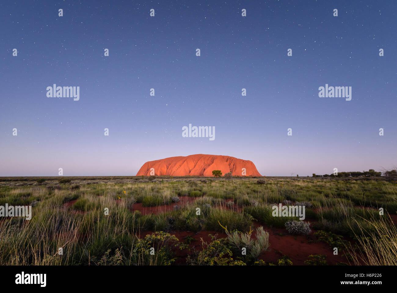 Uluru under night sky with stars - Stock Image