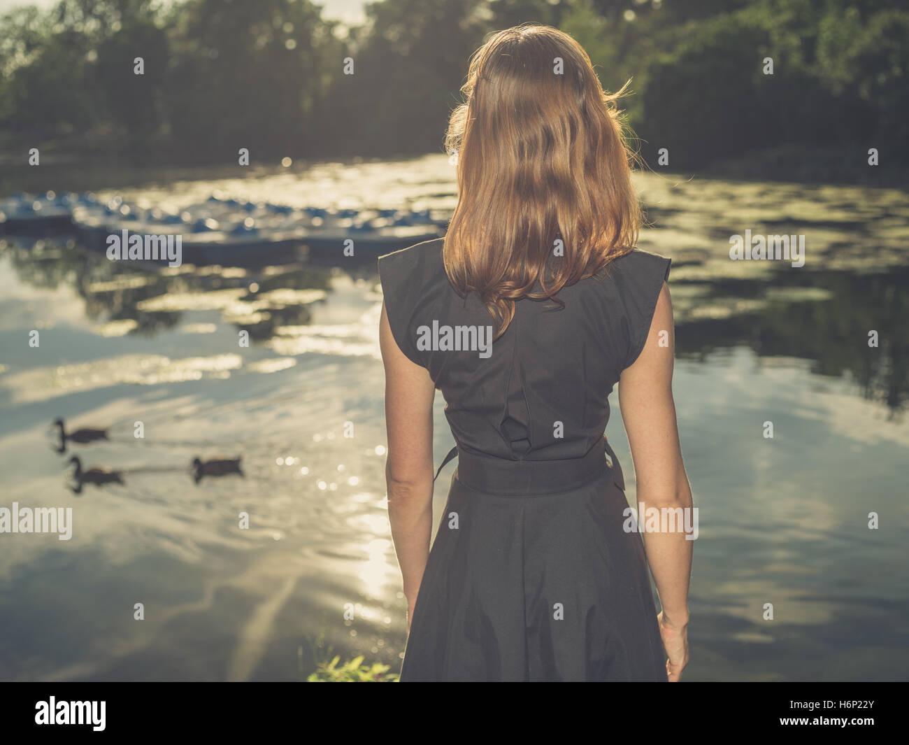 Vintage filtered shot of an elegant young woman standing by a lake in a park at sunset - Stock Image
