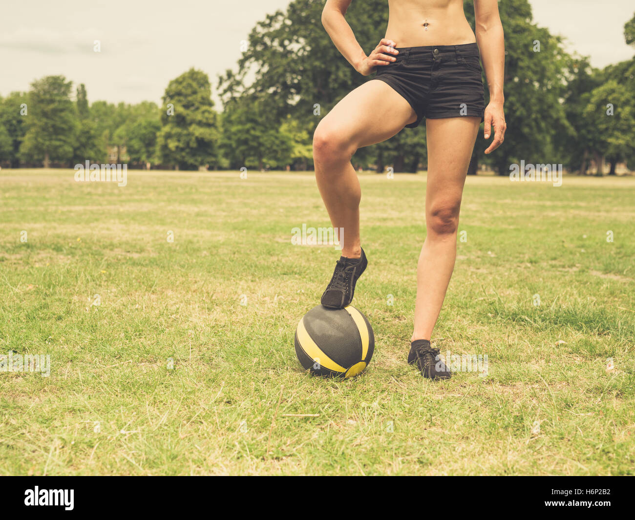 Vintage filtered shot of a fit and athletic young woman is standing on the grass in a park with a medicine ball - Stock Image