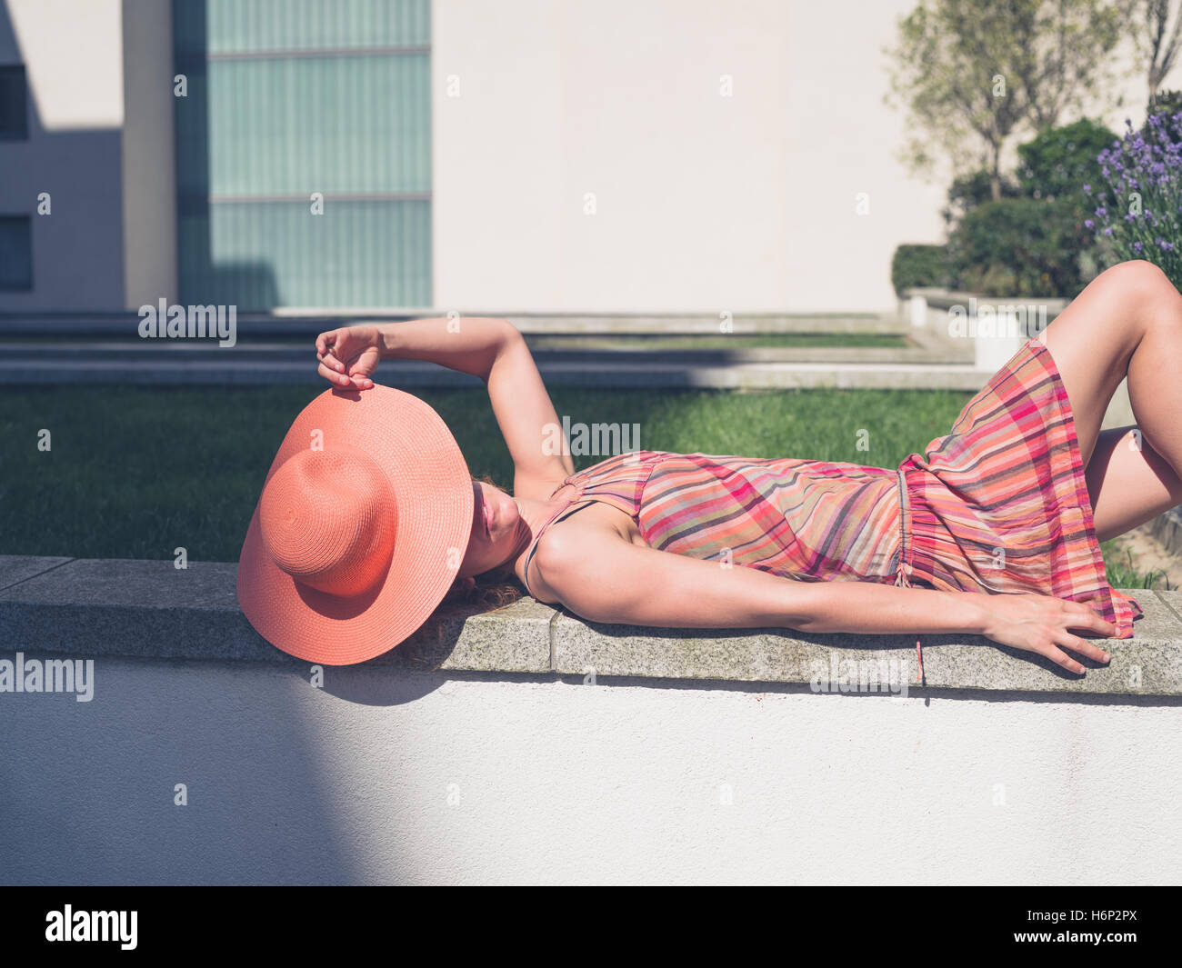 A young woman wearing a dress and a hat is relaxing outside on a sunny summer day - Stock Image