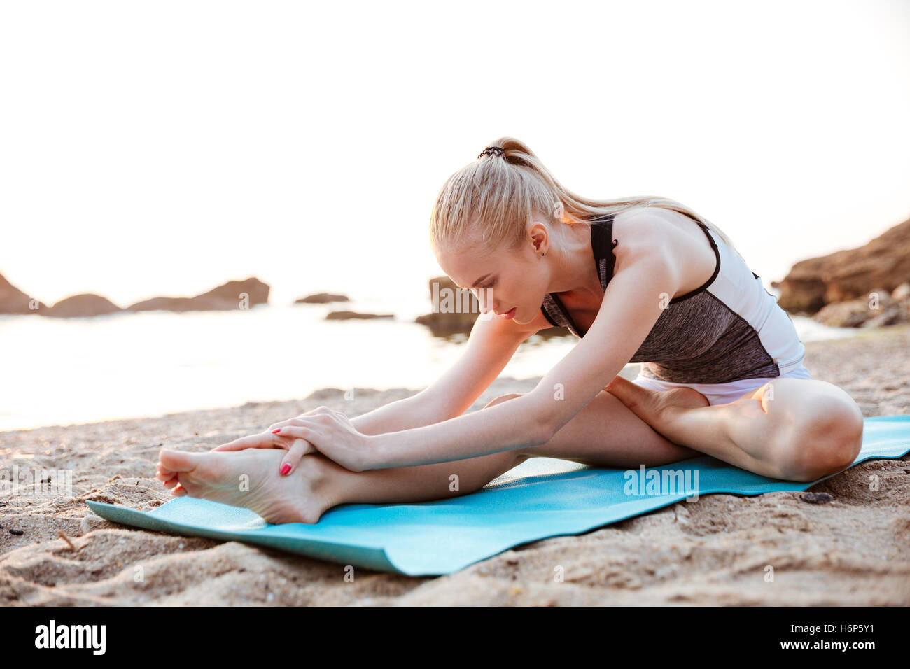Young woman doing yoga exercises on mat outdoors in the morning - Stock Image