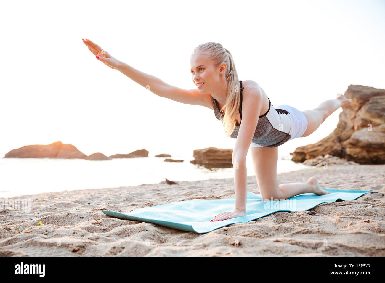 Portrait of a charming woman stretching on yoga mat on beach in the morning - Stock Image