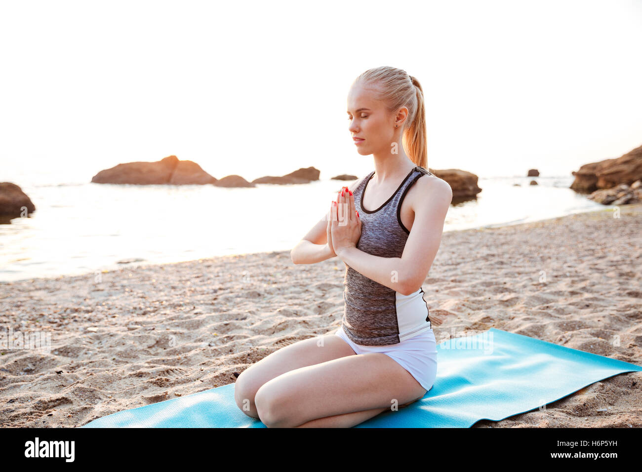 Portrait of relaxed young woman meditating outdoors on beach - Stock Image