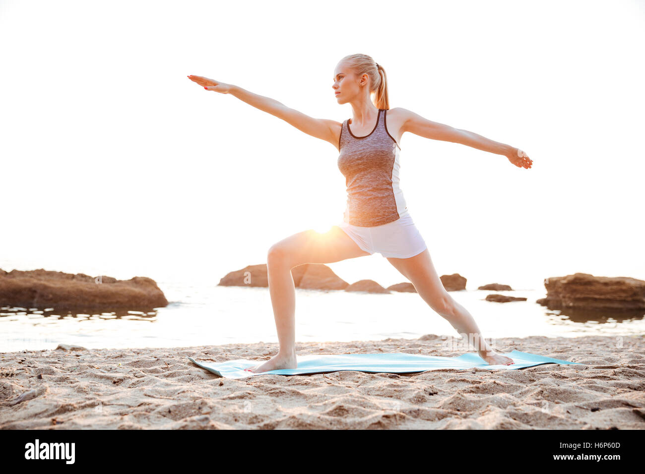Portrait of a concentrated young woman standing in yoga pose on beach - Stock Image