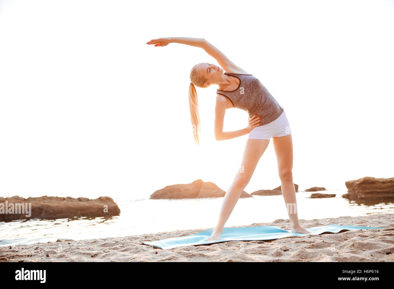 Beautiful young woman stretching hands during yoga on the beach - Stock Image